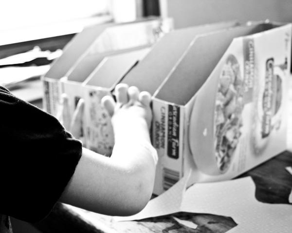 My child doing decoupage on her cereal box magazine organizer